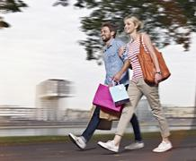 Germany, Cologne, Young woman and mid adult man with shopping bags Stock Photos