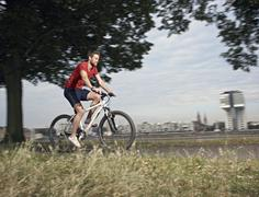 Germany, Cologne, Mid adult man riding bicycle - stock photo