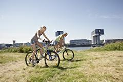 Germany, Cologne, Two Young women cycling bicycle Stock Photos