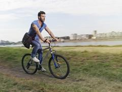 Germany, Cologne, Young man riding bicycle - stock photo