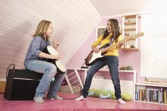 Girls playing guitar and drums, laughing - stock photo