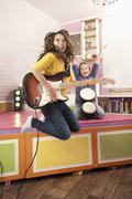 Girls jumping while playing guitar and drums Stock Photos