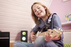 Girl playing guitar, smiling - stock photo