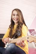Girl playing guitar, smiling, portrait Stock Photos