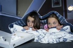 Girls hiding under bed sheet while watching scary film - stock photo