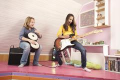 Girls playing guitar and drums, laughing Stock Photos