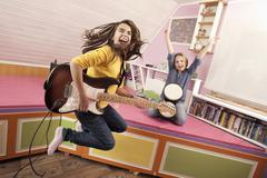 Girls jumping while playing guitar and drums - stock photo