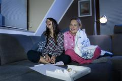 Girls laughing on couch with empty pizza box in front Stock Photos