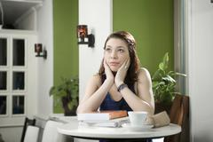 Germany, Bavaria, Munich, Young woman in cafe looking upset Stock Photos
