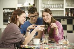 Germany, Bavaria, Munich, Young friends watching pictures in camera, smiling - stock photo