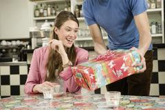 Germany, Bavaria, Munich, Young man surprising with gift to woman in cafe, - stock photo