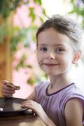 Stock Photo of Germany, Bavaria, Girl eating toast with chocolate cream, portrait