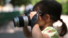 Baby girl takes pictures with dslr photo camera. Stock Footage
