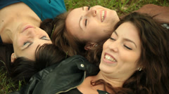 Three superb young adult women lay on grass. Stock Footage