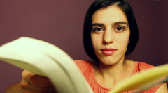 Young adult woman reads a book. Stock Footage