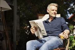 Stock Photo of Germany, Berlin, Mature man sitting on terrace and reading newspaper