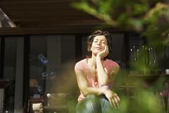 Germany, Berlin, Mature woman relaxing on terrace Stock Photos