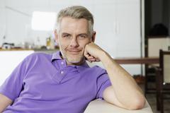 Germany, Berlin, Mature man sitting on sofa, smiling, portrait Stock Photos