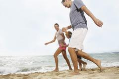 Stock Photo of Spain, Family walking on beach at Palma de Mallorca