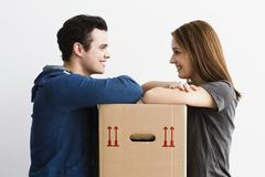 Stock Photo of Germany, Munich, Young couple leaning on cardboard box, smiling
