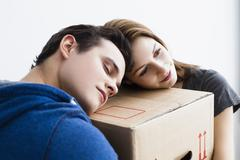 Germany, Munich, Young couple leaning on cardboard box, close up - stock photo