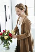 Stock Photo of Germany, Bavaria, Munich, Young woman arranging flowers in vase, smiling