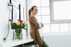 Germany, Bavaria, Munich, Portrait of young woman leaning on shelf, smiling Stock Photos