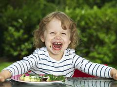Germany, Duesseldorf, Girl sitting outside and eating spinach, smiling, portrait - stock photo
