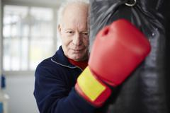 Germany, Duesseldorf, Senior man with boxing glove and punch bag Stock Photos