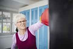 Germany, Duesseldorf, Senior woman with boxing glove and punch bag Stock Photos