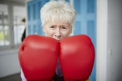 Germany, Duesseldorf, Portrait of senior woman with boxing glove Stock Photos