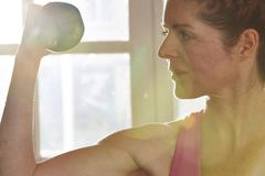 Germany, Duesseldorf, Mature woman exercising with barbell Stock Photos