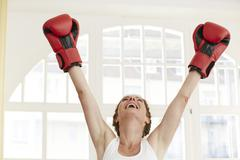 Germany, Duesseldorf, Mature woman with boxing glove Stock Photos