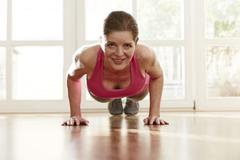 Germany, Duesseldorf, Mature woman doing push ups at home - stock photo