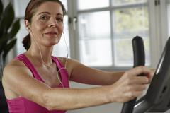 Germany, Duesseldorf, Mature woman exercising with treadmill, smiling portrait - stock photo