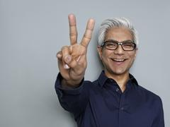 Businessman gesturing peace sign, smiling - stock photo