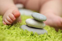 Baby feet next to stack of zen stones Stock Photos