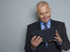 Stock Photo of Businessman looking at digital tablet, smiling