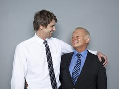 Stock Photo of Mid adult man looking at senior man, smiling