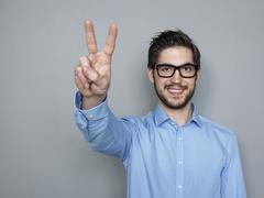 Businessman doing peace sign, smiling - stock photo