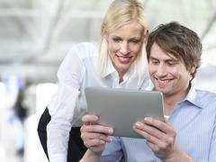 Businesscouple using digital tablet, smiling - stock photo
