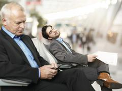 Senior man using mobile phone while mid adult man sleeping in background Stock Photos