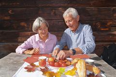 Germany, Bavaria, Senior couple eating alpine snack at mountain hut Stock Photos