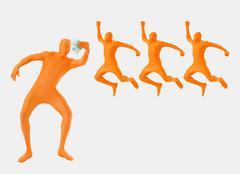 Man standing holding money in orange zentai while three men jumping in - stock photo