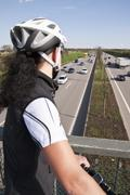 Germany, Mid adult woman with mountain bike on bridge looking at traffic on - stock photo