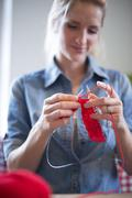 Stock Photo of Young woman knitting with red yarn