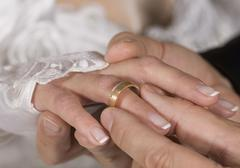 Man inserting wedding ring to wife, close up - stock photo