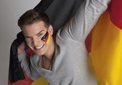 Young man with German flag, close up - stock photo