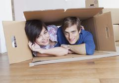 Stock Photo of Young couple in cardboard box, smiling, portrait