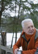 Germany, Senior man looks over fence Stock Photos